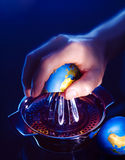 Hand squeezing earth globe on juicer Royalty Free Stock Image