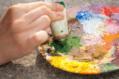 Hand squeezing green oilpaint on palette Royalty Free Stock Photos