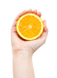 Hand squeezing an half of orange Royalty Free Stock Photo