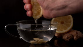Hand squeezing lemon into cup of hot water and ginger stock video