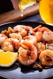 A hand squeezing lemon juice on roasted, grilled shrimp.  Royalty Free Stock Photography
