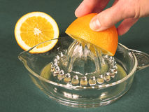Hand squeezing orange juice. In vintage glass juicer Royalty Free Stock Photos
