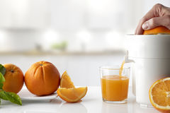 Hand squeezing an orange on a kitchen table horizontal composition. Hand squeezing an orange with an electric juicer in a glass on a white kitchen table. Oranges royalty free stock photo