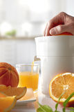 Hand squeezing an orange on a kitchen table vertical composition Stock Photography