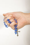 Hand squeezing rosary with cross Stock Photography
