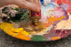 Hand squeezing yellow oilpaint on palette Royalty Free Stock Image