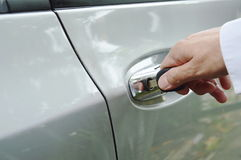 Hand stabbing car key in handle hole and twist for open door Royalty Free Stock Image