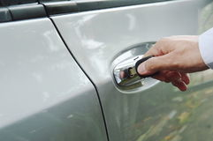 Hand stabbing car key in handle hole and twist for open door Royalty Free Stock Photo