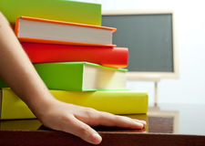 Hand and stack of colored book on the table Royalty Free Stock Photos