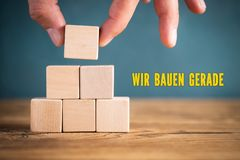 Hand is stacking blank cubes and the message `under construction ` in German royalty free stock image