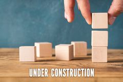 Hand is stacking blank cubes and the message `under construction ` stock images