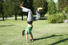 Hand Stand by Teen Boy. Teen boy doing hand stand on pretty lawn. Shot with Canon 20D royalty free stock photo