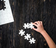 Hand starting to collect puzzle pieces. On dark wooden table stock images