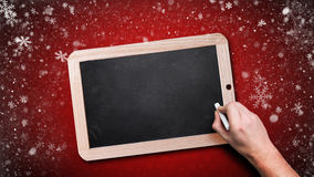 Hand starting to write on an empty chalkboard Royalty Free Stock Photos