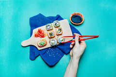 Hand with stcks on sushi set, isolated on blue background Stock Images