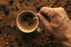 Hand steering coffee in a cup with spoon royalty free stock photos