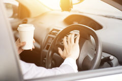 Hand on steering and honking. Concept photo of close up hand on steering honking while driving in morning, another hand holding coffee cup Royalty Free Stock Photography