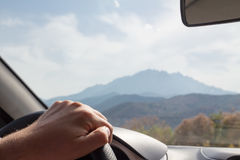 Hand on the steering wheel driving car with a landscape in the b. Ackground, Corsica, France Stock Images