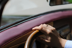 Hand on steering wheel of retro car. Hand on steering wheel of vintage, retro car. Man drives luxury vintage cars. A hand with a ring on the steering wheel. The Stock Photo