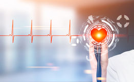 Hand with a stethoscope, heart HUD. Hand with a stethoscope and a bright red heart with HUD and infographics is seen against a blurred hospital background royalty free stock photo