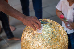 Hand sticking golden foil on sphere holy stone call loknimit Stock Photos