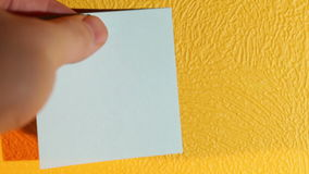 Hand sticks blank pink stick note on the yellow wall. stock video footage