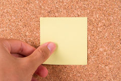 Hand and Sticky Post It Note. Hand and blank, yellow sticky post it note for your message on cork bulletin board royalty free stock images