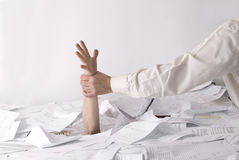 Hand stikking out of desk full of papers Royalty Free Stock Photography