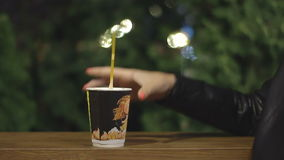 Hand stirs cappuccino in a paper cup stock video footage