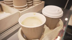 Hand stirs sugar with Spoon in disposable cup of soy latte coffee and covering it with plastic lid. Hand stirs sugar in disposable cup of coffee with a soy or stock footage