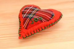 Hand-stitched festive heart, embroidered with the word JOY. Close-up of handmade festive pomander, embroidered with the word JOY, on a wooden table Stock Photo