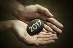 Hand with stone and number 2017 Royalty Free Stock Images