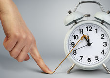 Hand stop time on alarm clock, deadline concept Royalty Free Stock Images