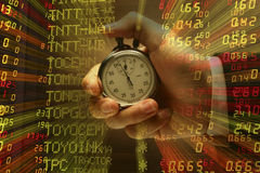 Hand with stop watch with stock index background Stock Photo