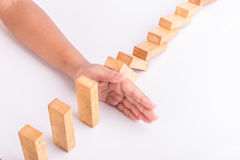 Hand stop wooden block. Domino risk effect concept royalty free stock photo