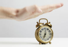 Hand stopping alarm on clock Royalty Free Stock Image