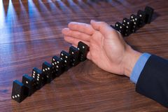 Hand stopping dominoes falling Royalty Free Stock Photography