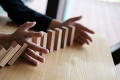 Hand stopping effect of domino continuous toppled. busineeman pr. Otecting falling wood block. solution & strategy in business. problem solving concept royalty free stock photo