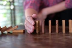 Hand stopping effect of domino continuous toppled. woman protect. Ing falling wood block. solution & strategy in business. problem solving concept stock photo