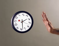 Hand stopping flying clock Royalty Free Stock Image
