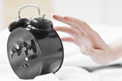 Hand stopping the morning clock Royalty Free Stock Photography