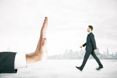 Hand stopping walking businessman. Miniature on city background Royalty Free Stock Images