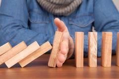 Hand stoppt Domino-Effekt lizenzfreie stockfotografie