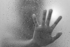 Hand of stranger on frosted glass with water drop. Behind the window stock image