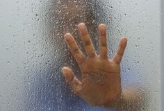 Hand of stranger on frosted glass with water drop. Behind the window royalty free stock photography
