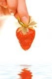 Hand with a strawberry Stock Images