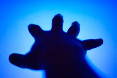 Hand stretching to TV screen Royalty Free Stock Photography