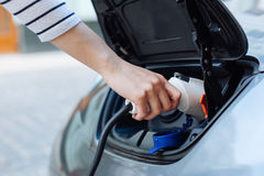 Hand in a striped jersey holding a charger for e-car Royalty Free Stock Photography