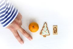 New Year concept 2019. Hand with a striped sleeve, mandarin, cookies Christmas trees and number nine stock photo