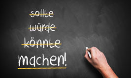 """Hand is stroking """"should, could, would'' and writes """"do!"""". Hand is stroking """"should, could, would'' and writes """"do!"""" in German Stock Photo"""